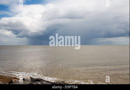 Heavy rain showers falling on sea from nimbocumulus cloud Orford Ness, North Sea, Suffolk coast, England - Stock Photo