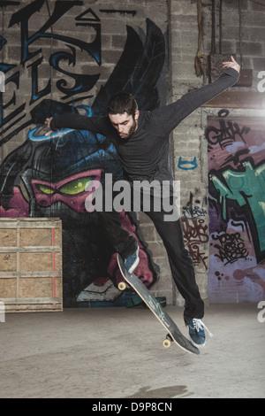 Skater doing impressive backside half cab 180 trick - Stock Photo