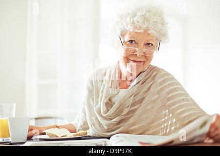 Happy senior woman reading her morning newspaper - Stock Photo