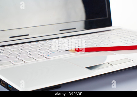 Pencil on a laptop keyboard - Stock Photo
