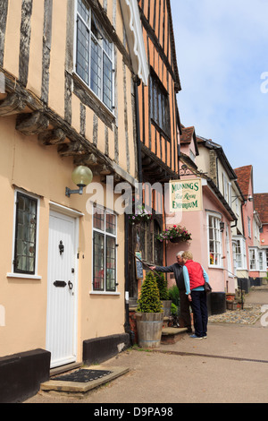 Two people studying the menu outside Munnings Tea Room Emporium in historic village centre. High Street Lavenham - Stock Photo