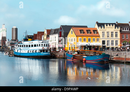 The old port of Husum with small and big ships, tourists and shops in the background - Stock Photo