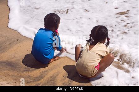 Asia, India, Tamil Nadu,  Mahabalipuram two girls playing on the beach in the water - Stock Photo
