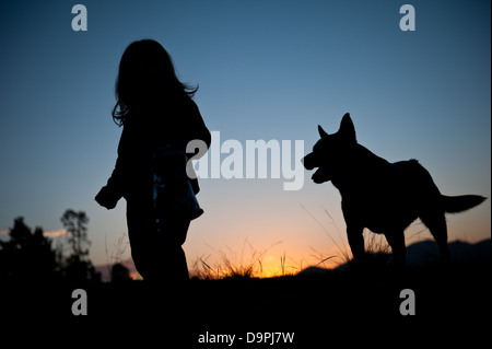 Beautiful sunset silhouette of young toddler girl with wavy hair walking in the field with her dog closely behind - Stock Photo
