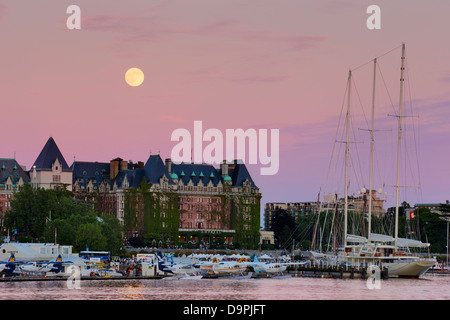 Full moon rising behind Empress hotel and luxury yacht Athena  at dusk-Victoria, British Columbia, Canada. - Stock Photo