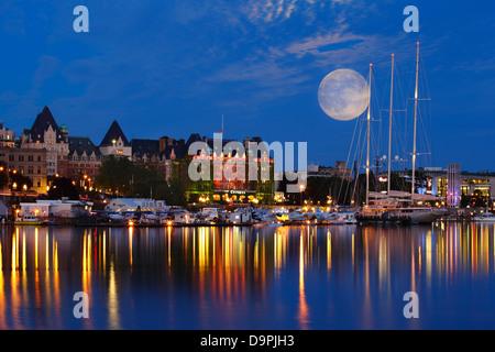 Full moon rising behind Empress hotel and luxury yacht Athena  at dusk-Victoria, British Columbia, Canada.  Digital - Stock Photo