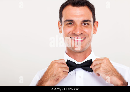 handsome waiter holding bow tie closeup - Stock Photo