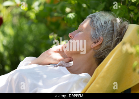 Aged woman with white hairs sleeping on lounger in her garden. - Stock Photo