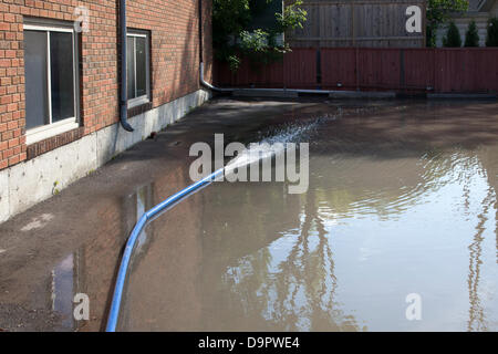 Saturday, June 22, 2013. Floodwater is pumped from the basement of an apartment building as cleanup begins in the - Stock Photo
