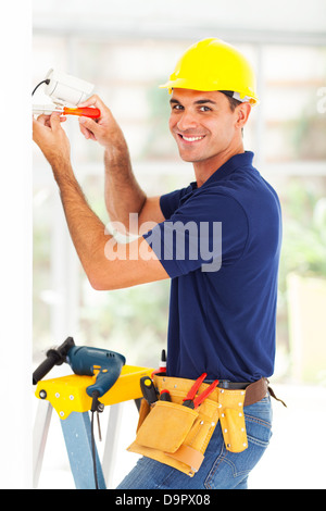 happy cctv system technician installing camera - Stock Photo