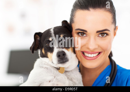 caring female vet holding a dog closeup portrait - Stock Photo