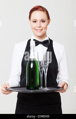 pretty young waitress holding tray with champagne and glass - Stock Photo