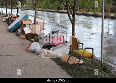 Waterlogged household items pile up along Memorial Drive as cleanup begins after floodwaters recede from the Sunnyside - Stock Photo