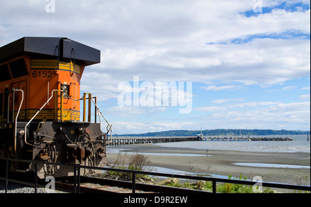 Train locomotive moving along the BNSF railway line that follows the beach in White Rock, BC, Canada. Also pier - Stock Photo