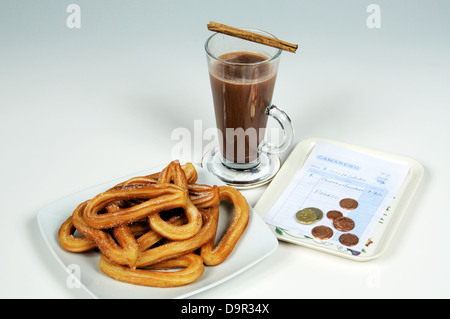 Churros with hot chocolate and a receipt, Mijas Costa, Costa del Sol, Andalucia, Spain, Western Europe. - Stock Photo