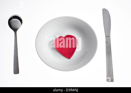Heart shape paper on a plate with a knife and fork - Stock Photo