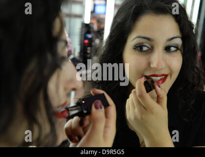 ILLUSTRATION - An illustrated picture shows beauty expert Fatma Liman putting on lipstick in a branch of perfume - Stock Photo