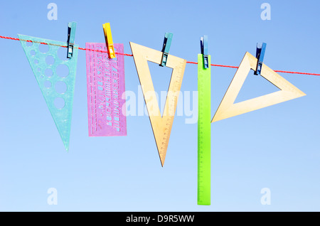 wooden and plastic rulers on washing line against sky - Stock Photo