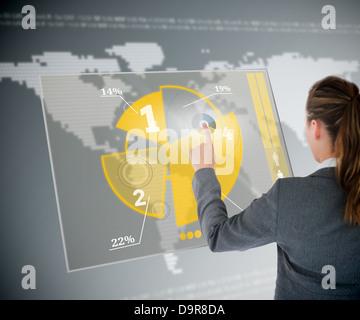 Well dressed business woman using yellow pie chart futuristic interface - Stock Photo