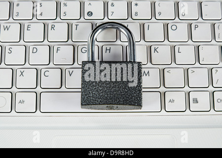 Padlock on top of a laptop keyboard - Stock Photo