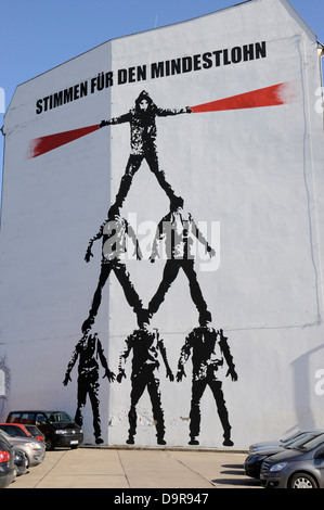 'Vote for the minimum wage' mural by Victor Ash on a wall in Schiffbauerdamm, Berlin - Stock Photo
