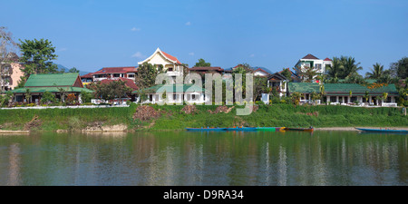 Horizontal panoramic (2 picture stitch) view of the riverside hotels and bars along the Nam Song river in Vang Vieng. - Stock Photo