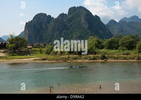 Horizontal view of activities on the Nam Song river in Vang Vieng on a sunny day. - Stock Photo