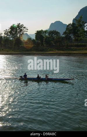 Vertical view of a motor boat travelling down the Nam Song river in Vang Vieng at sunset. - Stock Photo