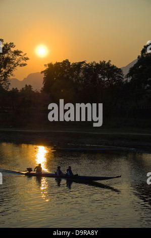 Vertical view of a motor boat travelling down the Nam Song river in Vang Vieng at sunet. - Stock Photo