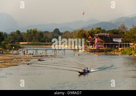 Horizontal view of activities on the Nam Song river in Vang Vieng at sunset. - Stock Photo