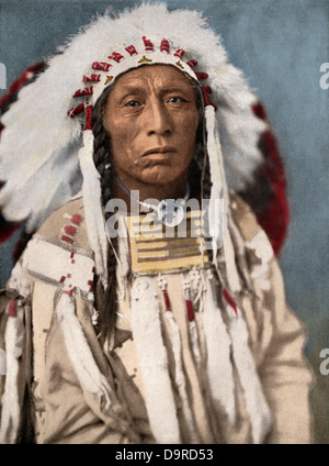 Crow Indian chief in a traditional war bonnet and clothing, circa 1900. Hand-colored halftone of a photograph - Stock Photo