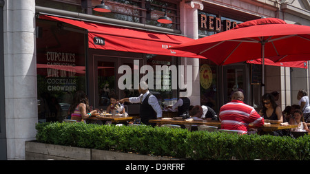 Patrons sit at the outdoor cafe of the Red Rooster restaurant on Lenox Avenue in the neighborhood of Harlem in New - Stock Photo