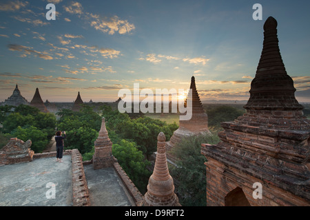 Wendy taking a picture of the Temples of Bagan at sunrise, Myanmar (Burma) - Stock Photo