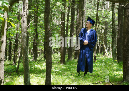 graduate student standing in forest - Stock Photo