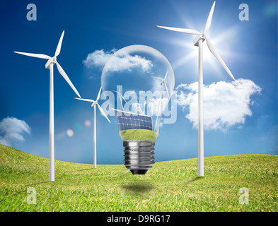 Light bulb showing solar panels and turbines in a field with wind turbines - Stock Photo