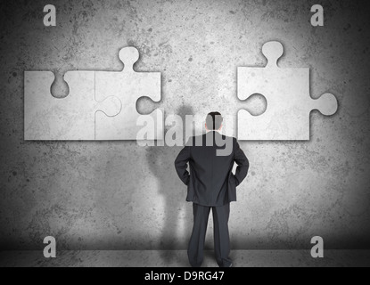 Businessman figuring out puzzle pieces - Stock Photo