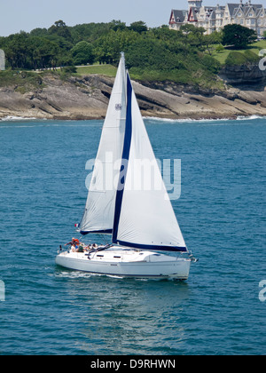 Sailing off Santander in a small twin sail yacht with Santander coast in the background - Stock Photo
