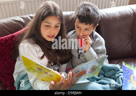 Older sister reading a story to her brother - Stock Photo