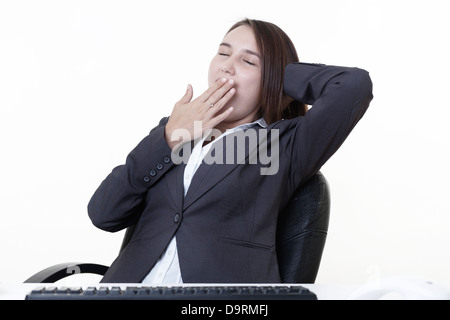 very young looking woman at her desk yawning  - Stock Photo