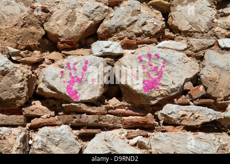 Child's handprint on stone wall in pink paint - Stock Photo