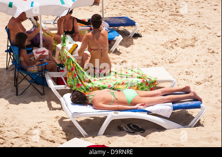 Israel Tel Aviv beach scene bikini clad girls women sunbathing sunbathe sand lounger loungers sun chairs - Stock Photo