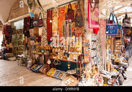 Israel Jerusalem Old City street scene Jewish Muslim Arab Christian tourist memorabilia souvenir shop stall in street - Stock Photo