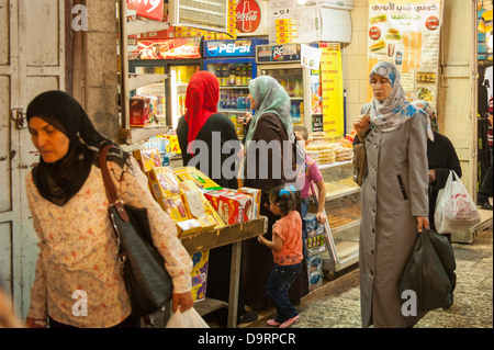 Israel Jerusalem Old City busy street road lane covered market scene Arab women walking shopping clothes hijab robes - Stock Photo