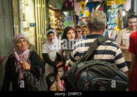 Israel Jerusalem Old City busy street road lane covered market scene tourists & Arab women walking clothes hijab - Stock Photo
