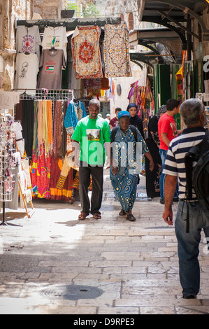 Israel Jerusalem Old City busy street road lane market souk street scene tourists walking clothes hijab robes thorbs - Stock Photo