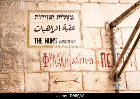Israel Jerusalem Old City typical street sign in Hebrew Arabic & English The Nuns Ascent & Greek ? painted directions - Stock Photo