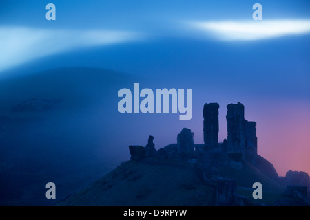 Corfe Castle in the mist at dawn, Dorset, England, UK - Stock Photo