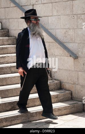 Israel Jerusalem Old City Ultra Orthodox Jewish bearded man walking down steps to Western Wailing Wall Ha Kotel - Stock Photo