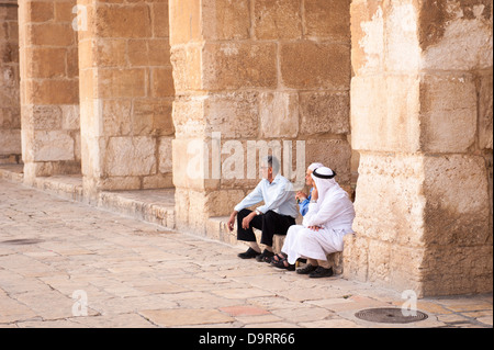 Israel Old City Jerusalem Haram Esh Sharif Noble Sanctuary Temple Mount Dome of the Rock group of men chat in shade - Stock Photo
