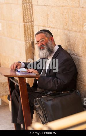 Israel Jerusalem Old City bearded Orthodox Jew sitting by lectern praying prayer book Wailing Western Wall Ha Kotel - Stock Photo